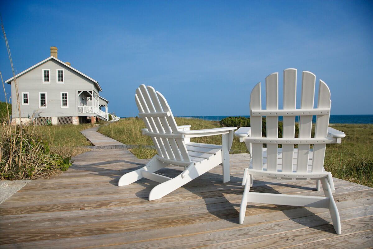 a beach house with a dock and two chairs