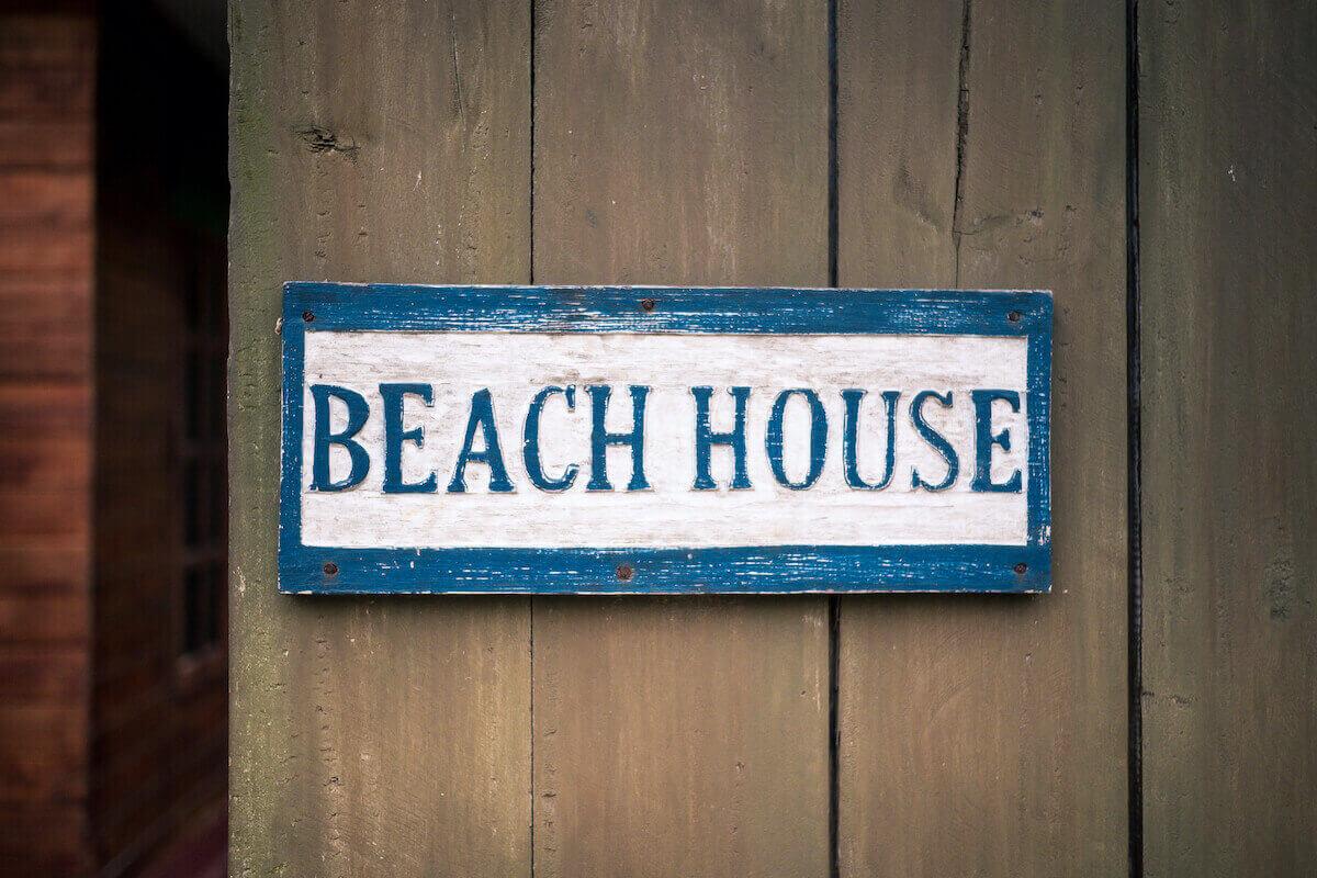 a wooden beach house sign