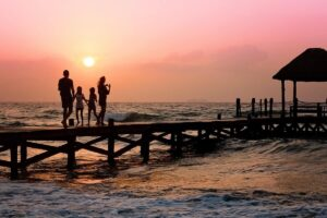 couple with two young kids on a boardwalk during a sunset