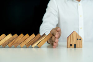 insurance with hands protect a house. Home insurance or house insurance