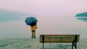 person under umbrella next to body of water